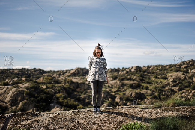 Pretty young woman standing on cliff