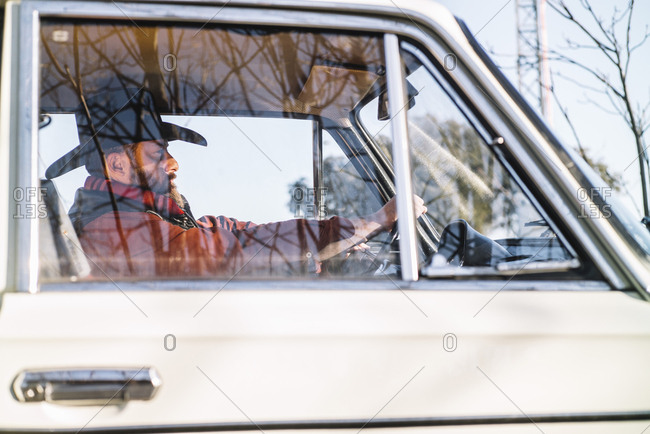 Handsome adult man in hat driving vintage white car in nature.