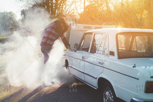Side view of adult man opening hood of smoking broken vintage car in nature.