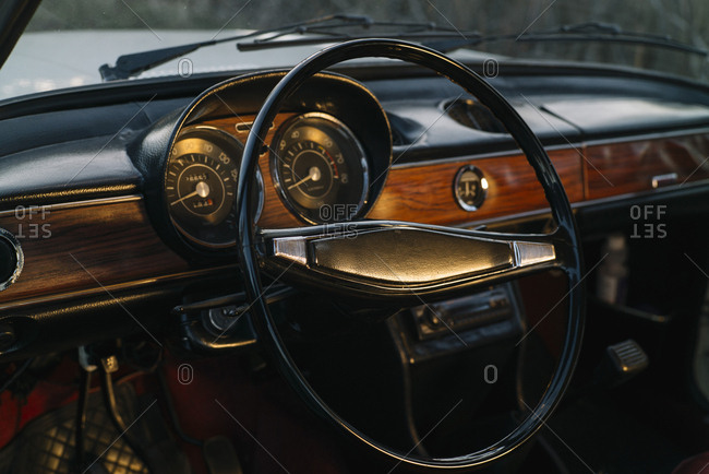 Dashboard with wooden panels and steering wheel of retro car.