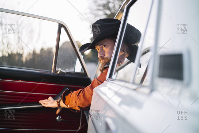 Thoughtful adult man in hat sitting in white vintage car with opened door in countryside.