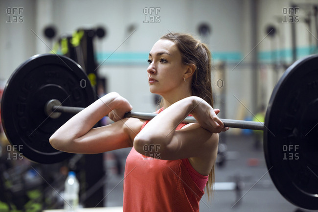 Pretty young fit woman standing with barbell while working out in the gym.