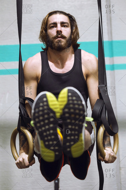 Handsome adult fit man hanging on rings while training in the gym.