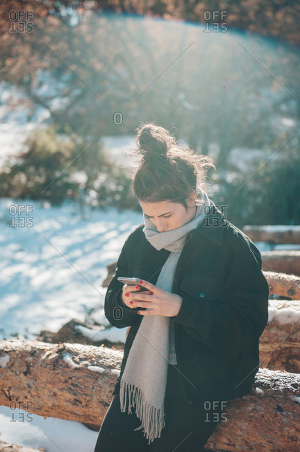 A pretty girl walking on a wooden trunks with snow