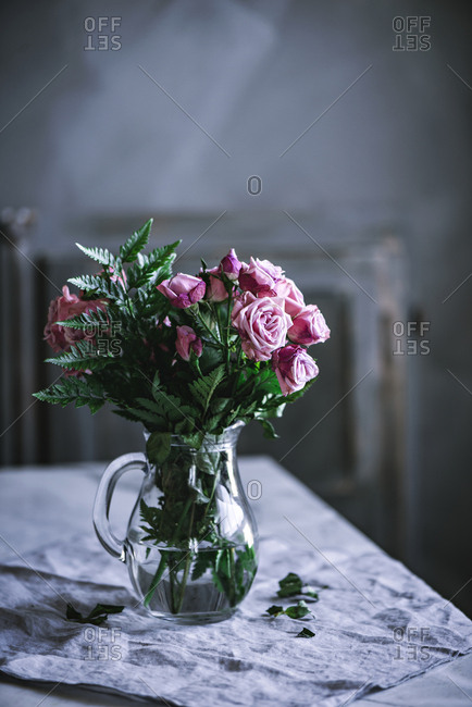 Bunch of fresh soft pink roses in glass jug on a table.