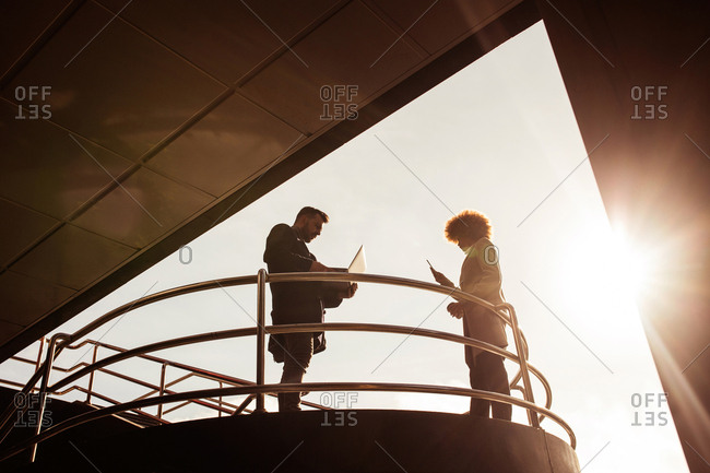 Couple with laptop at handrail