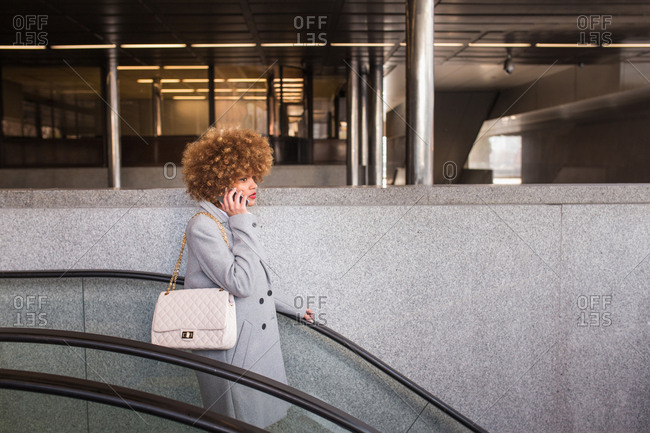 Side View Of Adult Stylish Woman Talking On Smartphone And Riding Down On Moving  Stairs.