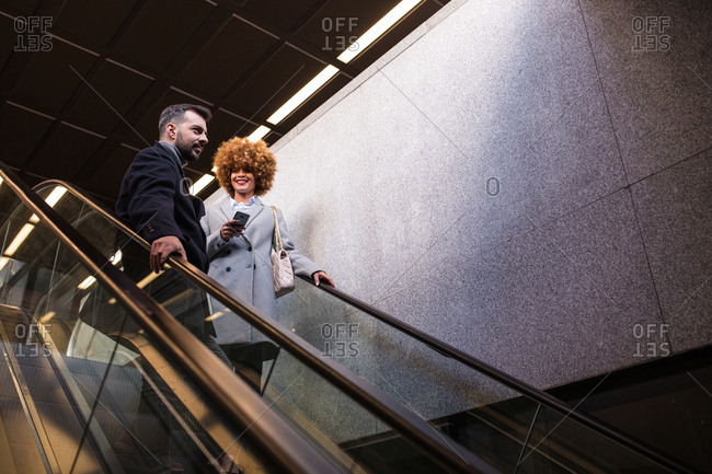 Adult stylish man and woman with smartphone riding down on moving stairs.