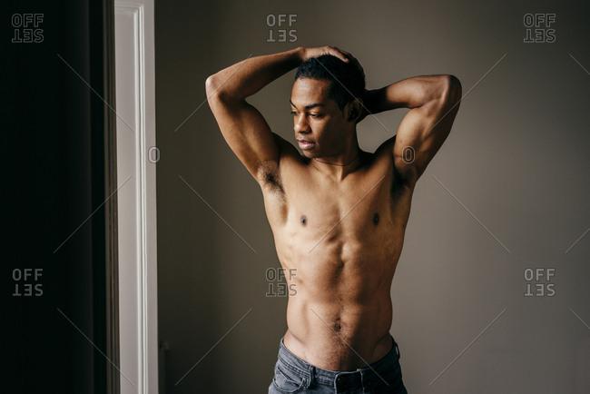Shirtless black man at window
