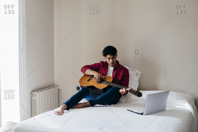 Young Asian man sitting and playing guitar on bed at laptop at home.