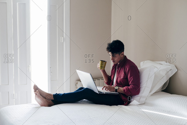 Young Asian man sitting on bed and using laptop with cup at home.