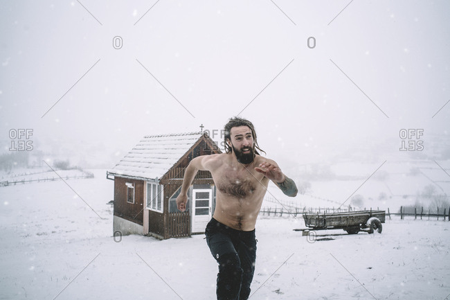 Man with a beard runs through the snow.
