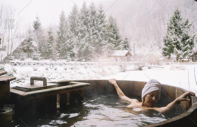 Pretty girl in thermal baths snowy landscape.