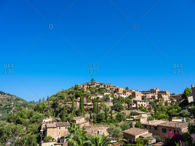 Panoramic view to small houses built in mountains covered with green in sunny day.