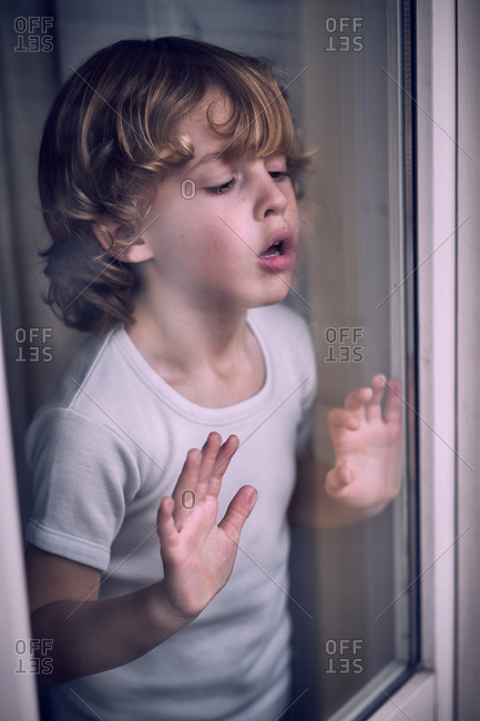 Cute little preschooler boy standing and breathing on window at home.