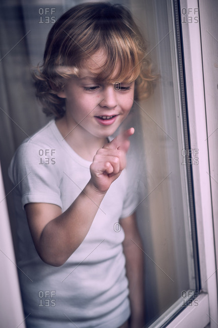 Little boy writing at window