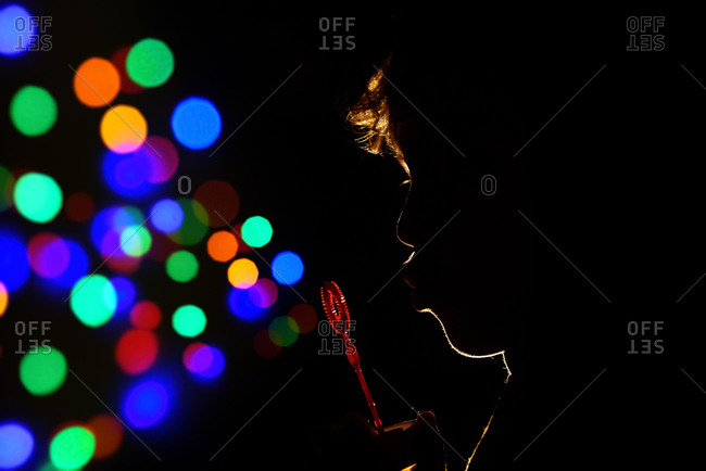 Silhouette of child blowing colorful bubbles