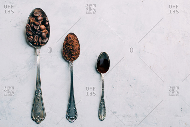 Coffee beans, ground coffee and black coffee in retro spoons