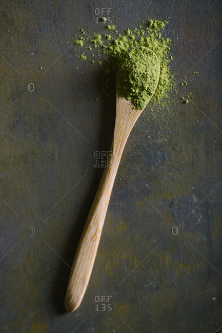 Bamboo scoop with matcha tea on dark background
