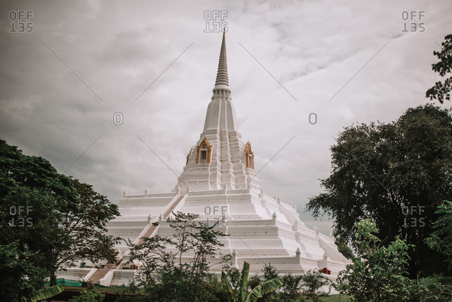 View to big spire of white traditional building in gray cloudy day.