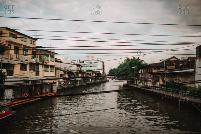 Perspective view to channel with dirty water and electric wires in cloudy day.