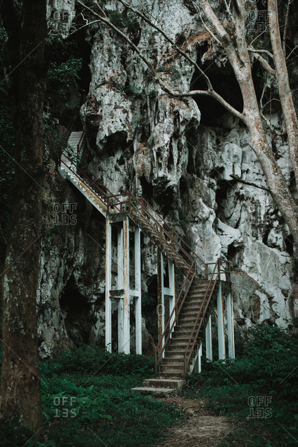 Old staircase leading to amazing stony cliff in beautiful nature.