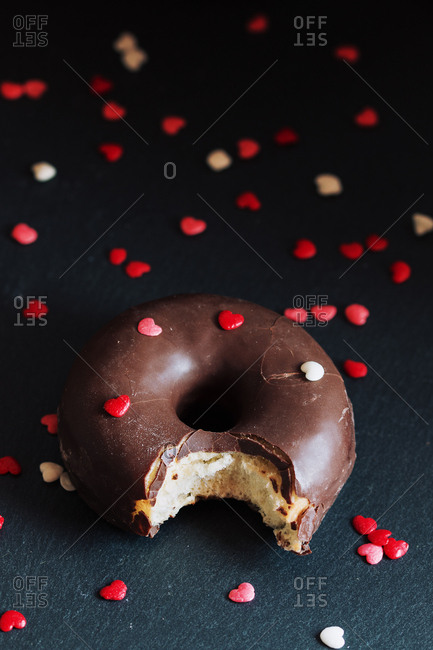 Bitten chocolate donut with toppings