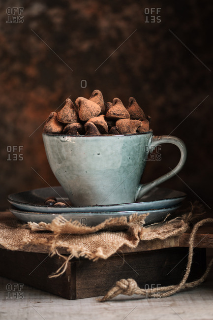 Chocolate truffles in a cup over a wooden box