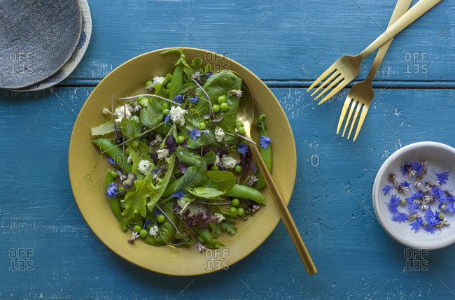 Green salad with peas, feta and edible flowers in a bowl with a serving spoon