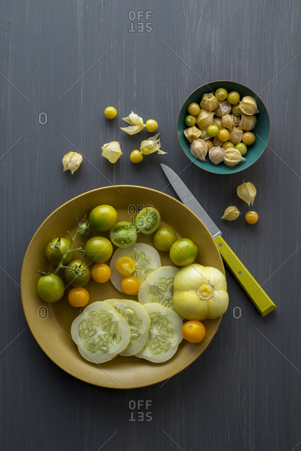 Husk cherries on a dark gray painted board with a bowl of cucumbers and cherry tomatoes