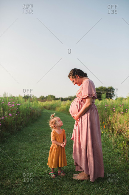 Pregnant mother smiling down at young daughter in country