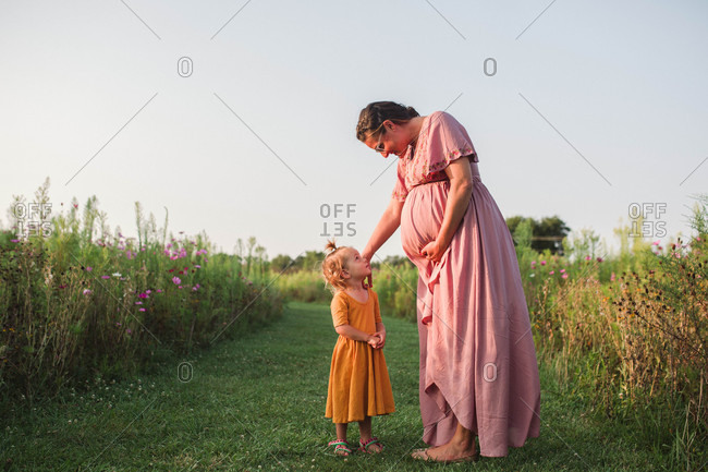 Expecting mom and little daughter sweetly looking at each other in grassy field