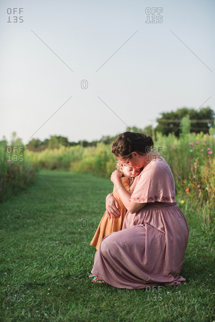Mom tenderly hugging daughter on grass
