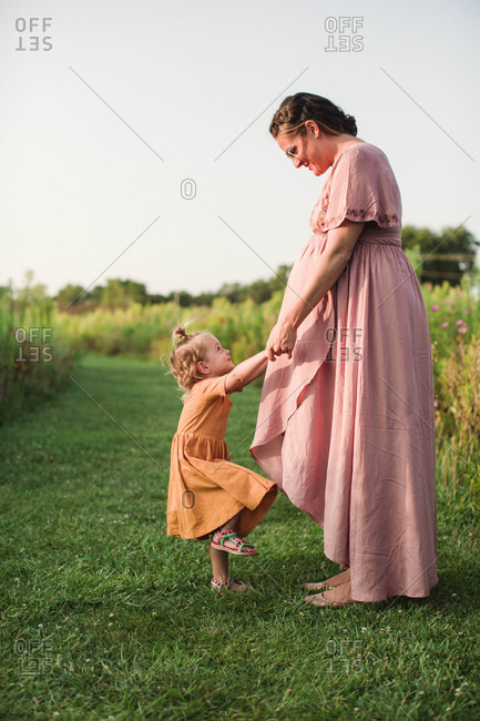Playful little girl pulling on pregnant mom's arms in field