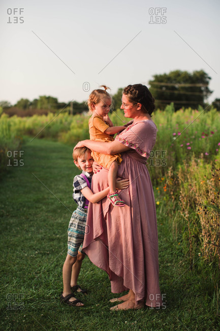 Brother and sister hugging mom at golden hour