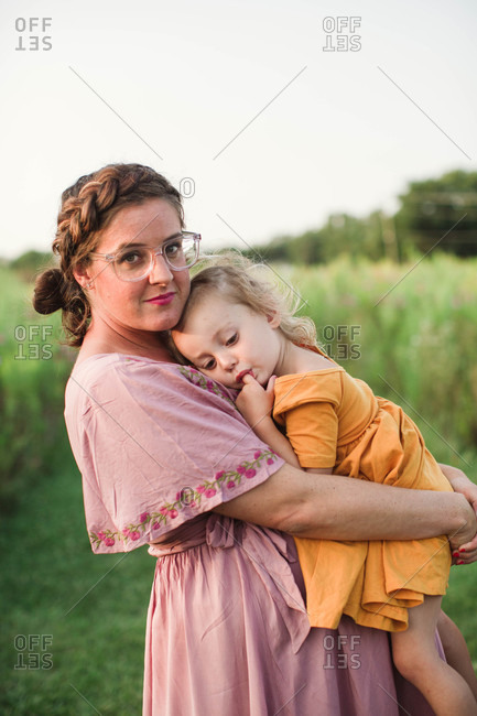 Proud pregnant mom holding sleepy daughter to chest in scenic grassy field