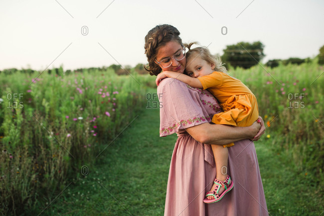 Cute tired girl wrapped around affectionate mom in the country