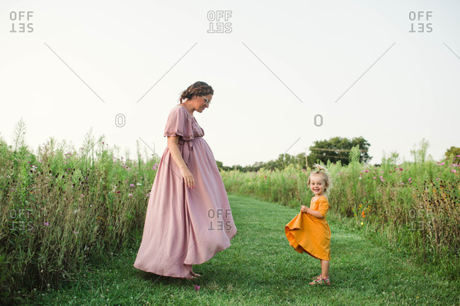 Family dancing and twirling dresses in field