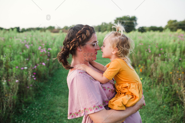 Mom and daughter nuzzling noses in field of wildflowers