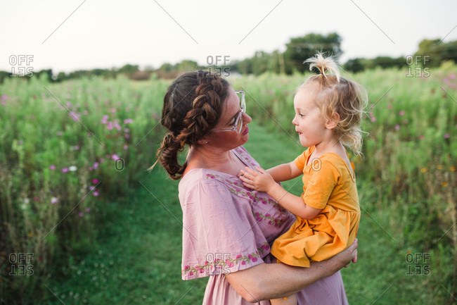 Small child making funny faces in moms arms at sunset