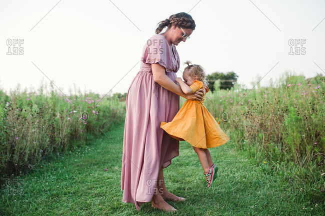 Candid maternity family portrait with mom lifting energetic daughter