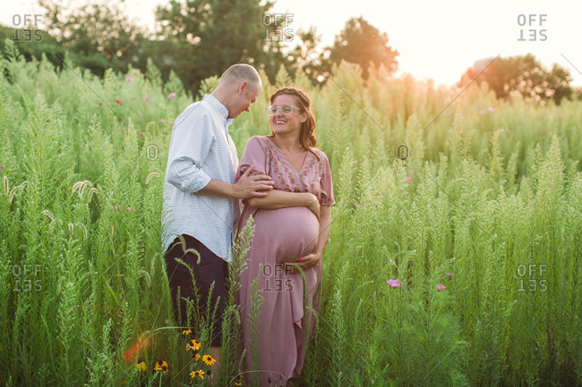 Husband and pregnant wife laughing in tall grass