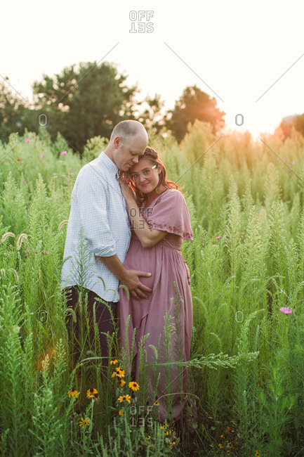 Loving portrait of expecting parents in field of tall grass