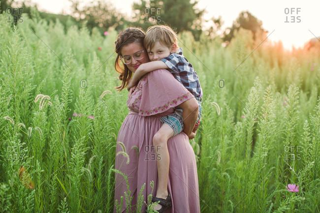 Pregnant mother tenderly holding older son on back at sunset