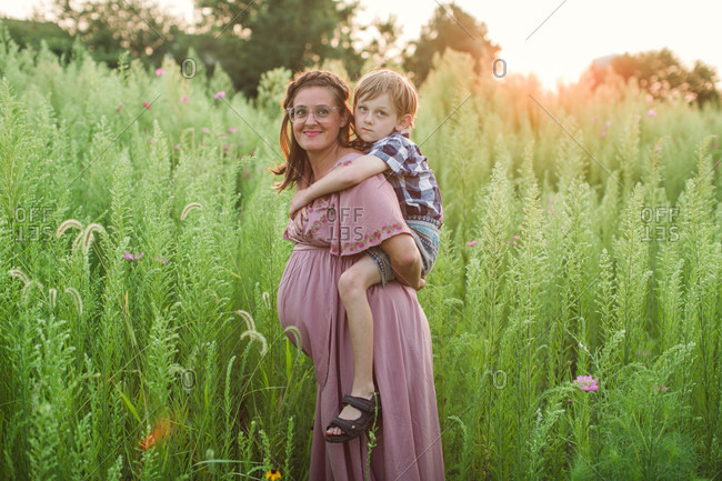 Sweet maternity portrait with mom carrying little boy on back