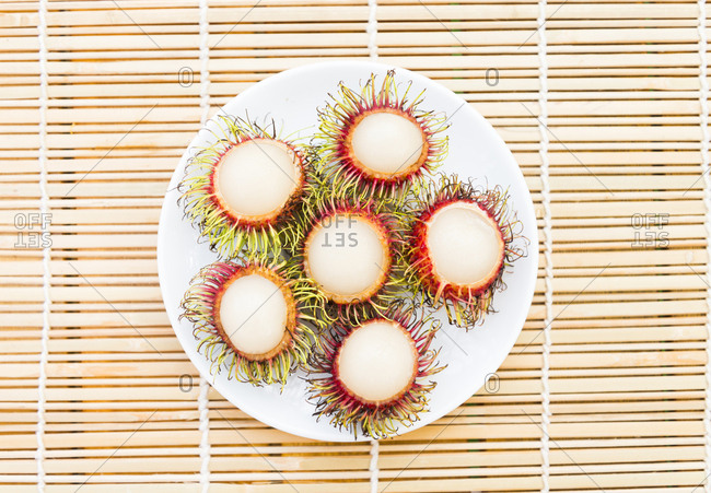 A plate of fresh Lychee fruit on a bamboo table mat