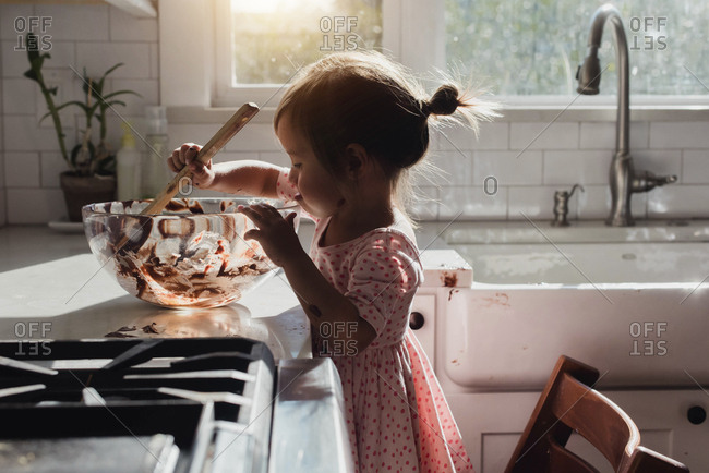 Toddler looking into mixing bowl while making brownies