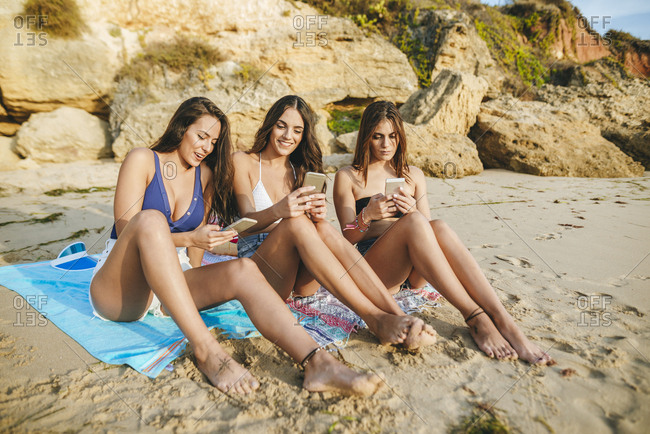 Three women using their mobile phones on the beach
