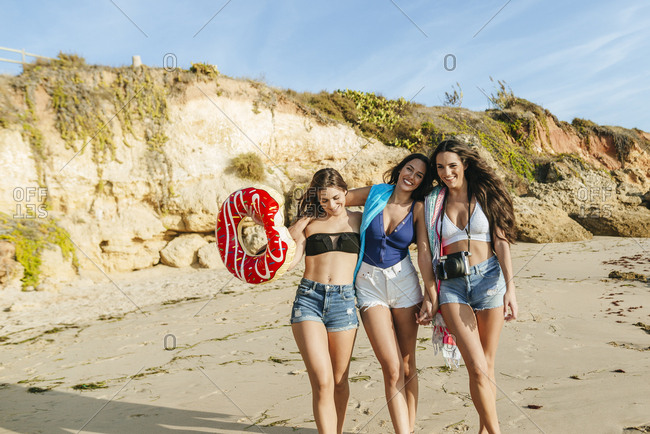 Three young girlfriends walking on the beach in summer
