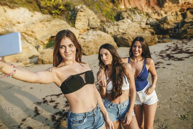 Three women taking a selfie on the beach